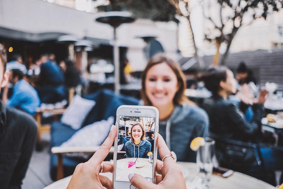 girl taking photo at cafe