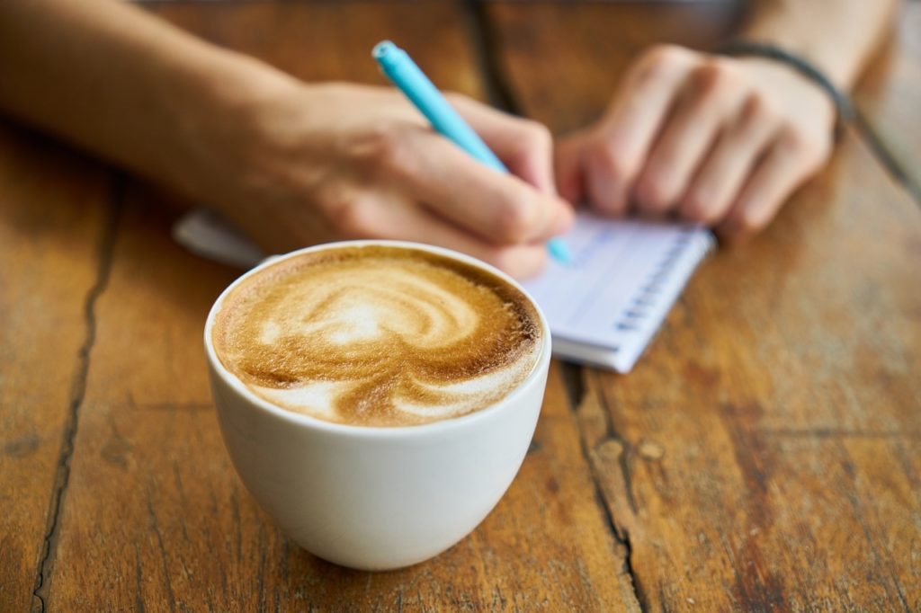 woman-writing-in-notebook-in-cafe