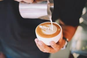 barista-pours-milk-into-coffee-to-make-latte-art