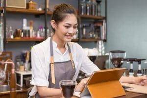 female-cafe-owner-uses-pos-tablet-to-stock-check